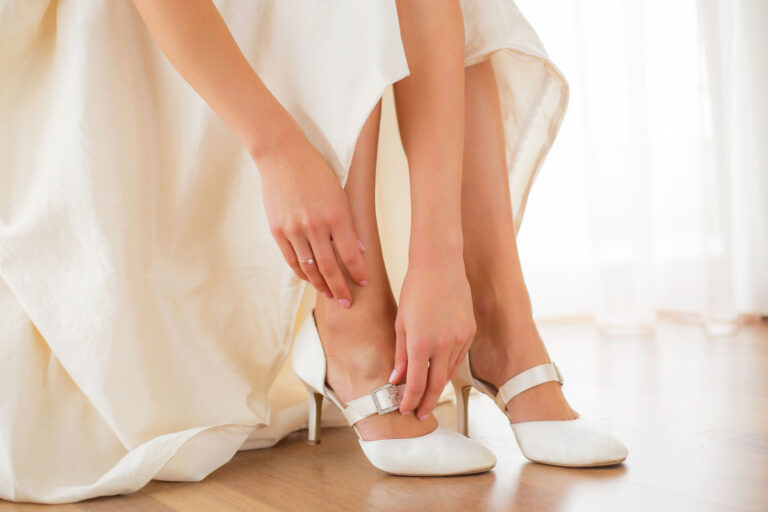 47035456 - bride putting on her white shoes